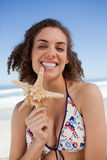 Smiling young woman proudly holding a starfish Royalty Free Stock Photography