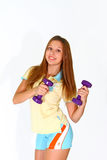 Smiling young woman with purple dumbbells Stock Photography