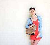 Smiling young woman with purse. Portrait of smiling young woman holding purse standing against white wall Stock Photos
