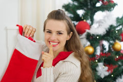 Smiling young woman put gift in Christmas socks Stock Images