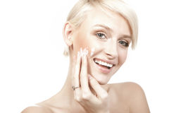 smiling young woman putting cream stock photography
