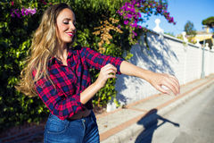 Smiling young woman putting her collar while standing on sunny street. Smiling young woman putting her collar while standing royalty free stock photography