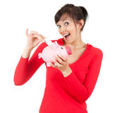 Smiling young woman putting money into piggy bank Stock Photo