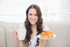 Smiling young woman in pyjamas having breakfast Royalty Free Stock Photos