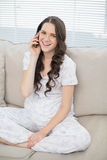 Smiling young woman in pyjamas having phone call Stock Photography