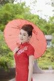 Smiling Young Woman in Qipao Holding Umbrella and Looking At Camera Royalty Free Stock Photos