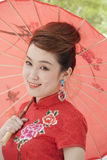 Smiling Young Woman in Qipao Holding Umbrella and Looking At Camera Stock Images