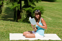 Smiling young woman read book in park Stock Photography