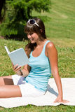 Smiling young woman read book in park. On sunny day sitting on blanket Royalty Free Stock Photos