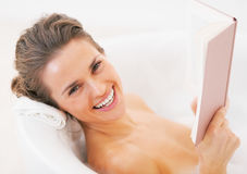 Smiling young woman reading book in bathtub Royalty Free Stock Image