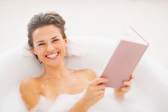 Smiling young woman reading book in bathtub Royalty Free Stock Photo