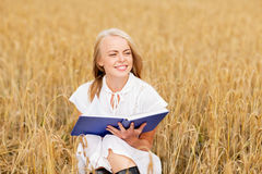 Smiling young woman reading book on cereal field Royalty Free Stock Photography