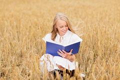 Smiling young woman reading book on cereal field Royalty Free Stock Image