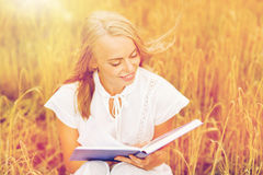 Smiling young woman reading book on cereal field Stock Photography