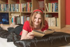 Smiling young woman is reading a book stock image