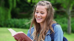 Smiling young woman reading a book stock footage