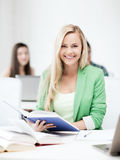 Smiling young woman reading book at school Stock Image