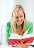 Smiling young woman reading book at school Stock Photos