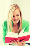 Smiling young woman reading book at school Royalty Free Stock Photo
