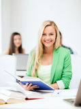 Smiling young woman reading book at school Stock Photography