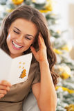 Smiling young woman reading christmas postcard Stock Photos