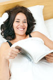 Smiling young woman reading in her bed Royalty Free Stock Photo