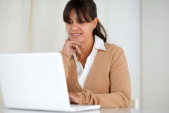 Smiling young woman reading on laptop screen stock photo