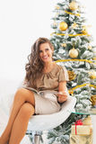 Smiling young woman reading magazine near christmas tree Royalty Free Stock Images