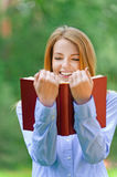 Smiling young woman reading red book Royalty Free Stock Photo