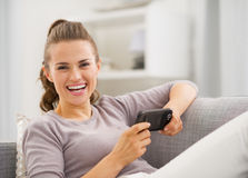 Smiling young woman reading sms while sitting on sofa Royalty Free Stock Photography