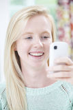 Smiling Young Woman Reading Text Message Royalty Free Stock Images