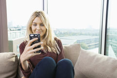 Smiling young woman reading text message at home Stock Image