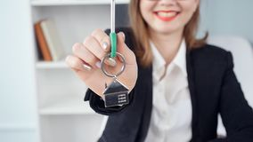 Smiling young woman realtor hands over the keys to new real estate. Smiling young woman realtor in office hands over the keys to new real estate stock footage