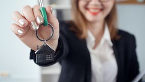 Smiling young woman realtor hands over the keys to new real estate