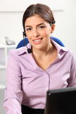 Smiling young woman receptionist in office royalty free stock photography