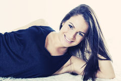 Smiling young woman reclining royalty free stock images