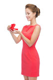Smiling young woman in red dress with gift box Stock Photos
