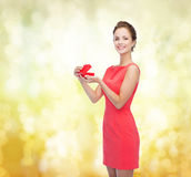 Smiling young woman in red dress with gift box Royalty Free Stock Images