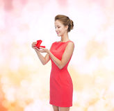 Smiling young woman in red dress with gift box Royalty Free Stock Photography