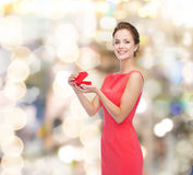 Smiling young woman in red dress with gift box Stock Photo