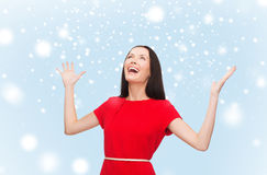 Smiling young woman in red dress with hands up Royalty Free Stock Photos