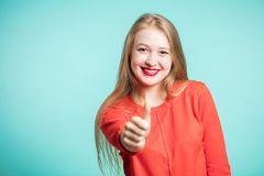Smiling young woman in red dress shows the thumbs up on a blue background stock photos