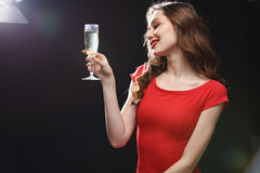 Smiling young woman in red dress standing and drinking champagne royalty free stock photos