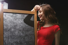 Smiling young woman in red dress standing near folding screen Royalty Free Stock Images