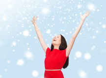 Smiling young woman in red dress waving hands Royalty Free Stock Photography