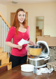 Smiling young woman in red with electric crock pot Stock Photos