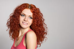 Smiling young woman with red hair on gray stock photo