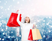 Smiling young woman with red shopping bags Royalty Free Stock Photo