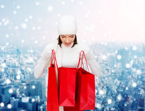 Smiling young woman with red shopping bags Stock Image