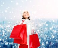 Smiling young woman with red shopping bags Stock Photography